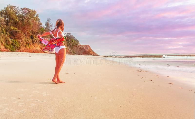 Woman on beach with beach towel flapping behind her royalty free stock photos