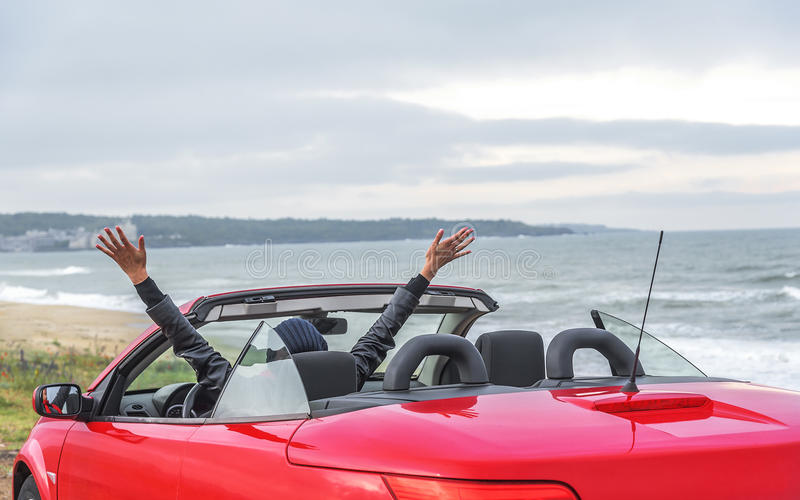 Woman on the beach in the cabriolet car. royalty free stock image
