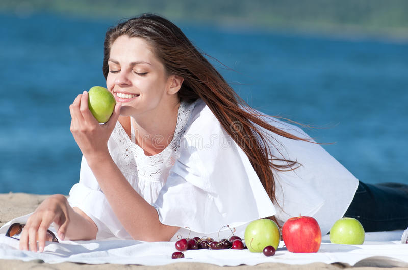 Woman on beach eating fruits royalty free stock photo