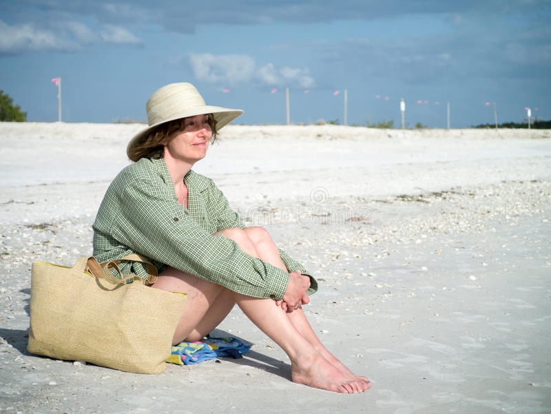 Woman on the beach enjoying the warm weather