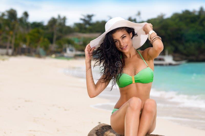 Woman on the beach in hat and bikini. Young woman on the beach in hat and bikini royalty free stock photo