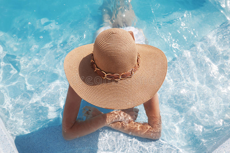 Woman in beach hat enjoying in swimming pool on luxury tropical. Resort. Exotic Paradise. Travel, Tourism and Vacations Concept stock image