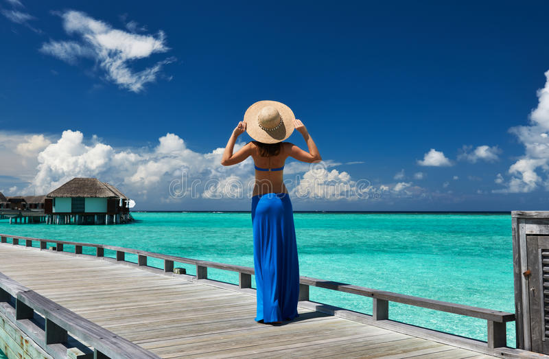 Woman on a beach jetty at Maldives royalty free stock images