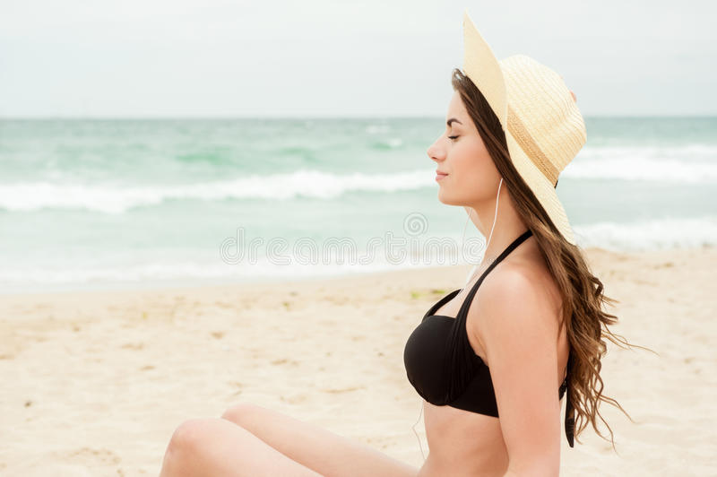 Woman on beach listening her head phones. Portrait of a young woman sitting on a white sand beach shore, listening to music with her head phones stock photos