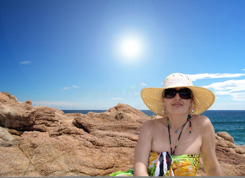 Woman on beach. Woman lying on the rocks on the beach on a summer day stock photography