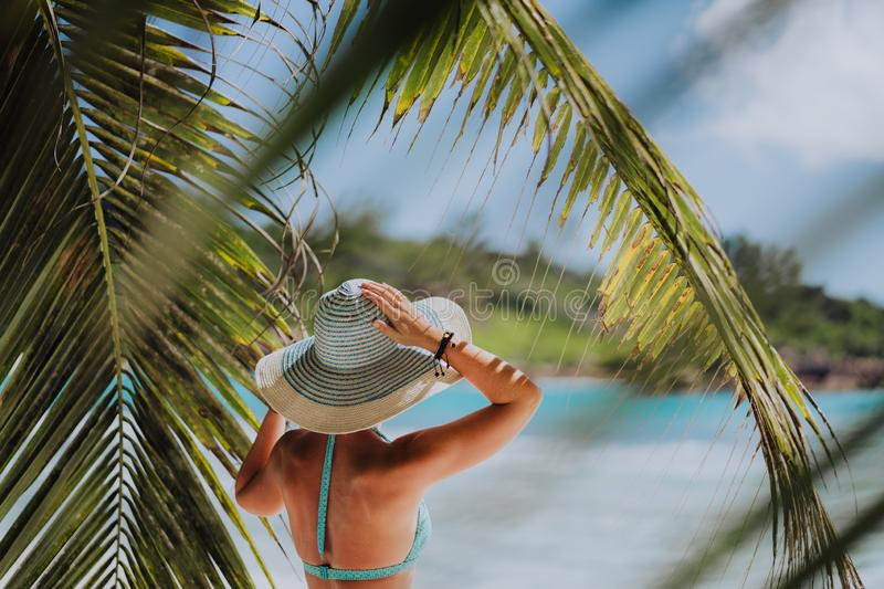 Woman on the beach in the palm trees shadow wearing blue hat. Luxury paradise recreation vacation concept stock photo