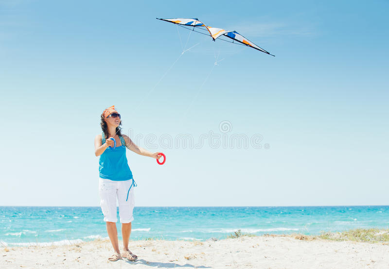 Woman On Beach Playing With A Colorful Kite Royalty Free Stock Photos