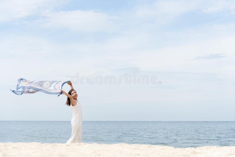 Woman on the beach, portrait of young happy woman wearing white dress and holding scraft on tropical sand beach. Summer Concept stock photography