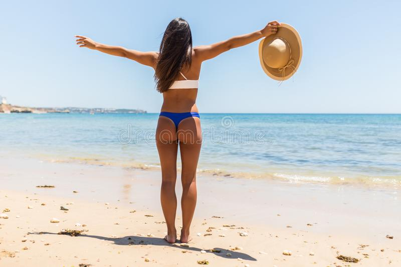 Woman on Beach standing with arms outstretched against turquoise sea. Rear view of female wearing bikini with raised hands. Carefr royalty free stock photo