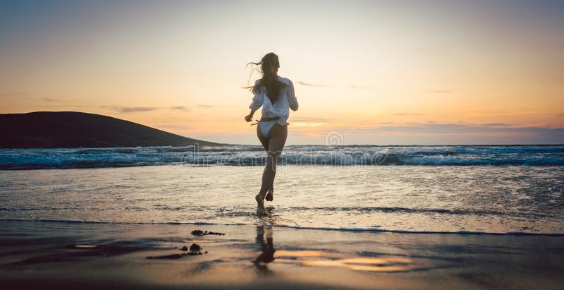 Woman at the beach in sunset entering the water. Woman at the beach in sunset running into the water stock photo