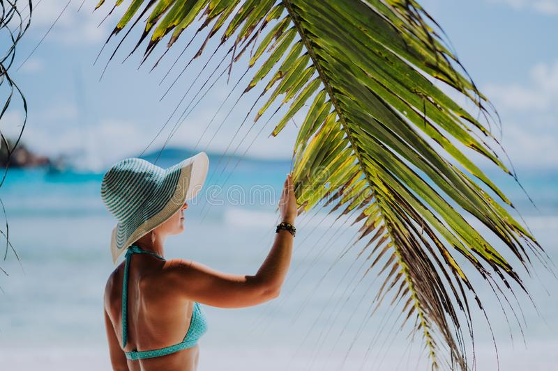 Woman on the beach touching palm tree leaf shadow wearing blue hat. Luxury paradise recreation vacation concept stock photos