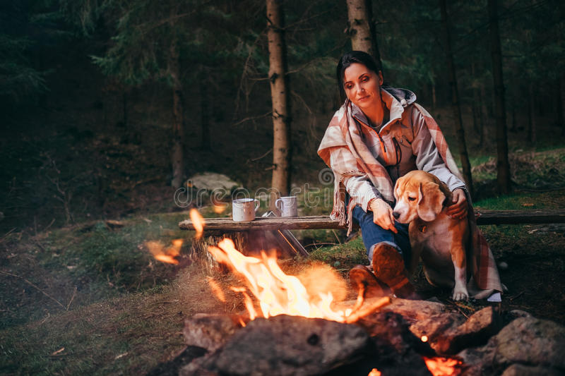 Woman with beagle dod swarms near the campfire. Woman with beagle dod warms near the campfire stock photos