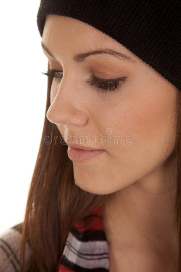 Woman in beanie and plaid shirt close side. A woman in a beanie looking down with a serious expression on her face stock photos
