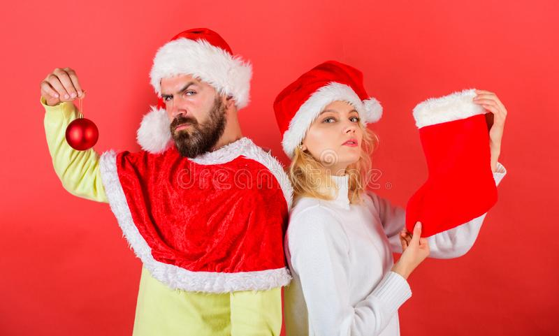 Woman and bearded man in santa hat waiting christmas red background. Christmas celebration concept. Christmas stocking stock photography