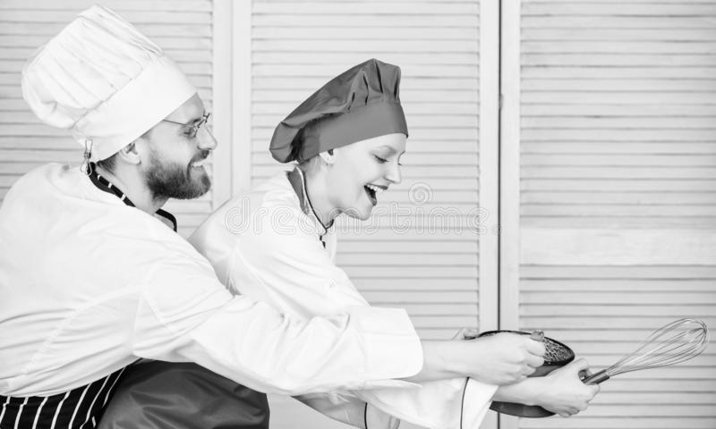 Woman and bearded man chef cooking together. Cooking healthy meal. Delicious meal. Baking pie together. Cooking together royalty free stock images