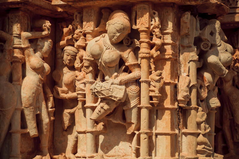 Woman beats the drum in stone. Woman beats the drum on the front of Hindu temple in Chitaurgarh Fort. City has population about 117,000 and the largest fort in stock image