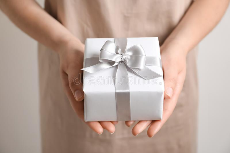 Woman holding gift box on light background. Woman beauiful holding gift box on light background stock image