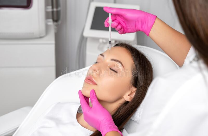 Woman at the beautician. Cosmetologist does anti wrinkle injections on the forehead and between eyebrows. Women`s cosmetology in royalty free stock image