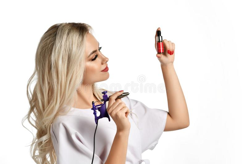 Woman beautician cosmetologist hold tattoo machine gun isolated on white. Background stock image