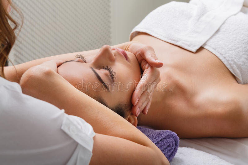 Woman beautician doctor make head massage in spa wellness center stock image