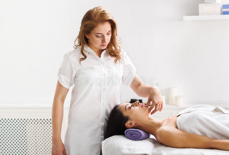 Woman beautician doctor make head massage in spa wellness center royalty free stock image