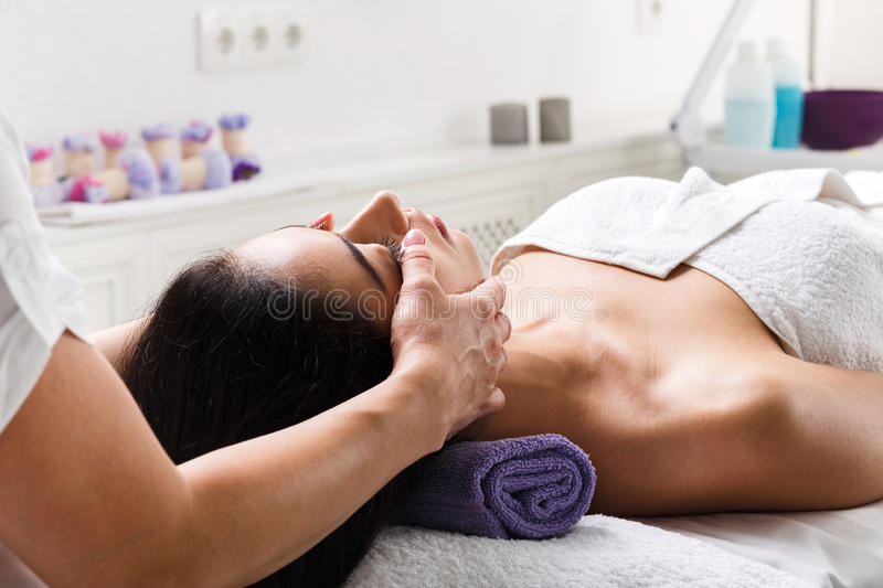 Woman beautician doctor make head massage in spa wellness center royalty free stock images