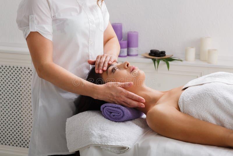 Woman beautician doctor make head massage in spa wellness center stock photo