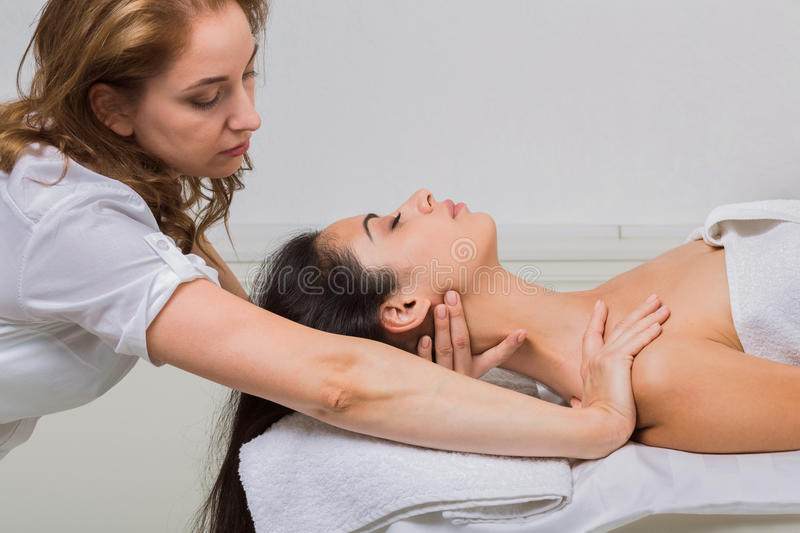 Woman beautician doctor make neck massage in spa wellness center. Female beautician with client in spa wellness center. Professional cosmetologist make body stock photo