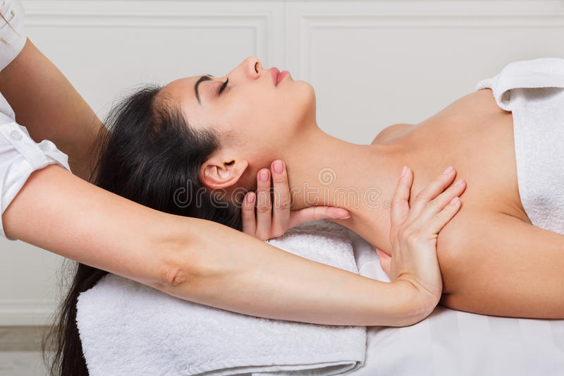 Woman beautician doctor make neck massage in spa wellness center. Unrecognizable female beautician doctor with patient in spa wellness center. Professional royalty free stock photography