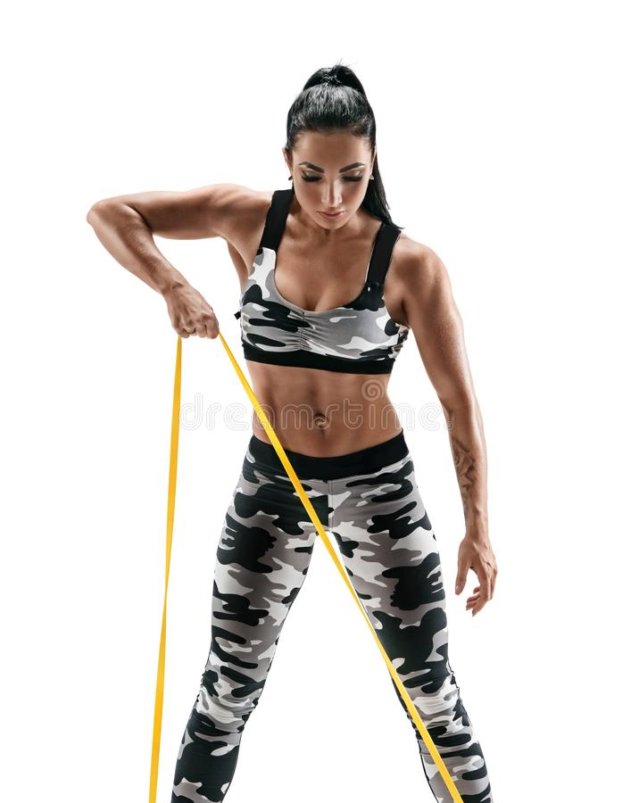 Woman with beautiful athletic body performs exercises using a resistance band. Photo of latin woman in military sportswear isolated on white background stock photo