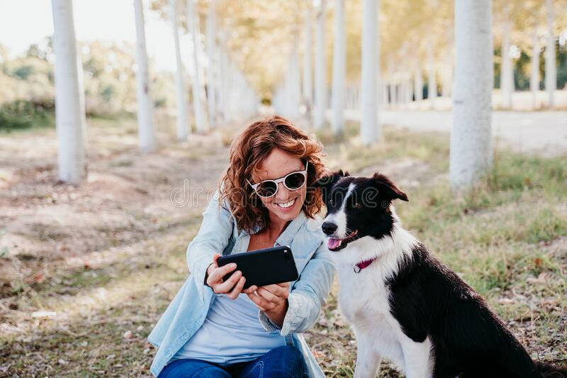 Woman and beautiful border collie dog sitting in a path of trees outdoors. woman taking a selfie with mobile phone royalty free stock photos