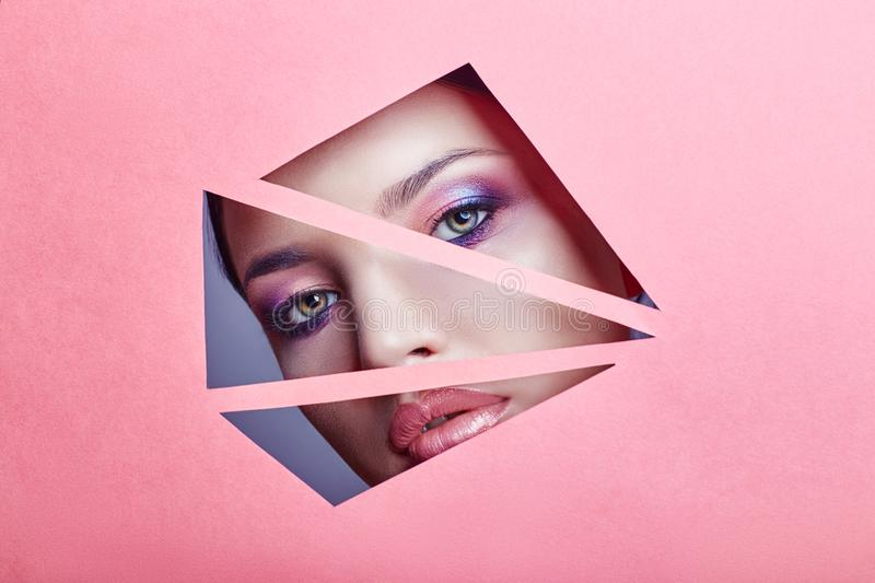 Woman with beautiful bright makeup and pink lipstick looks through triangular slits in pink paper. Advertising cosmetics, profess. Ional art makeup, lip gloss royalty free stock images