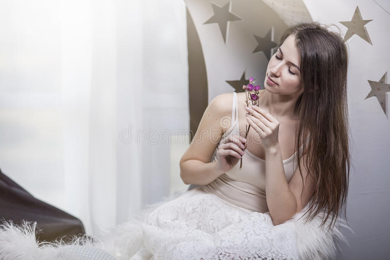 Woman beautiful brunette with flower in hand dried flowers in white clothes stock photos