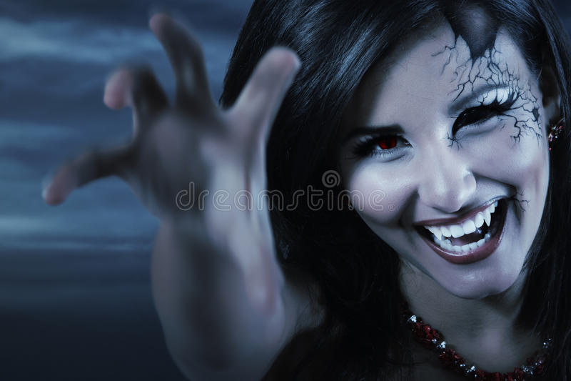 Woman beautiful halloween vampire. Woman beautiful halloween evil vampire over night background stock photos