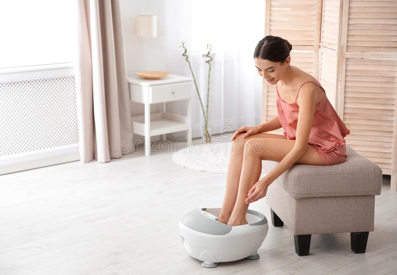 Woman with beautiful legs using foot bath at home royalty free stock photo