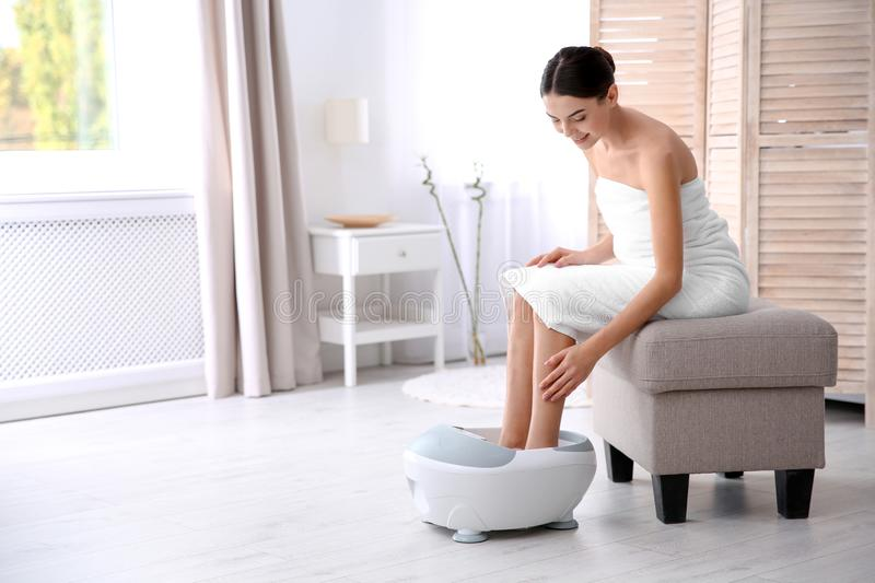 Woman with beautiful legs using foot bath at home royalty free stock image