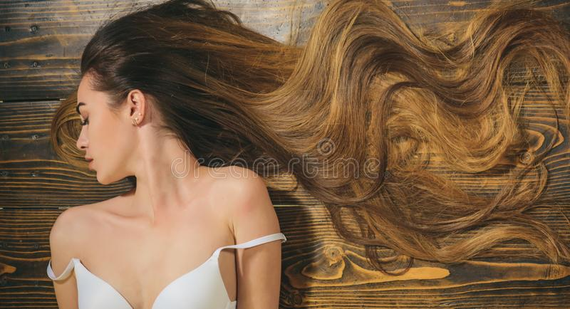 Woman with beautiful long hair on wooden background. Long hair. Closeup woman portrait with very long hair, copy space royalty free stock photo