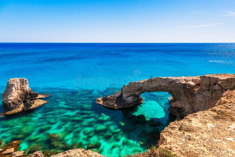Woman on the beautiful natural rock arch near of Ayia Napa, Cavo Greco and Protaras on Cyprus island, Mediterranean Sea. Legendary. Bridge lovers. Amazing blue stock images