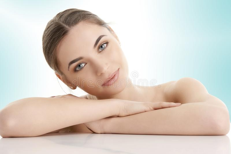 Woman with beautiful skin. Portrait of gorgerous woman face with perfect skin looking at camera while posing against at isolated light blue background stock images