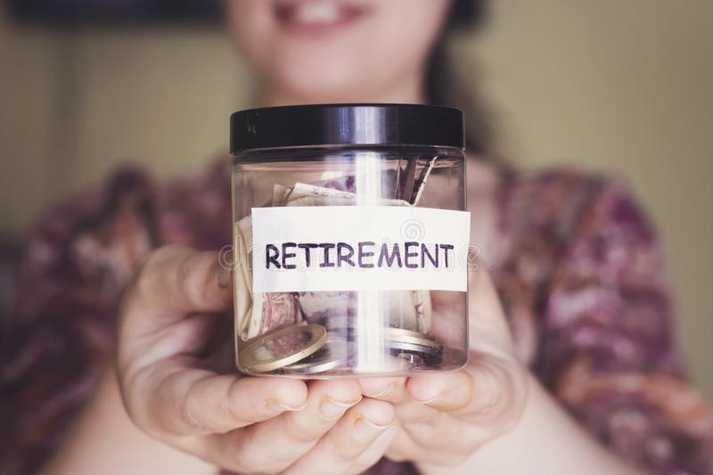 Woman with beautiful smile hold a retirement plastic jar for save money. Woman with beautiful smile hold a retirement jar for save money stock image