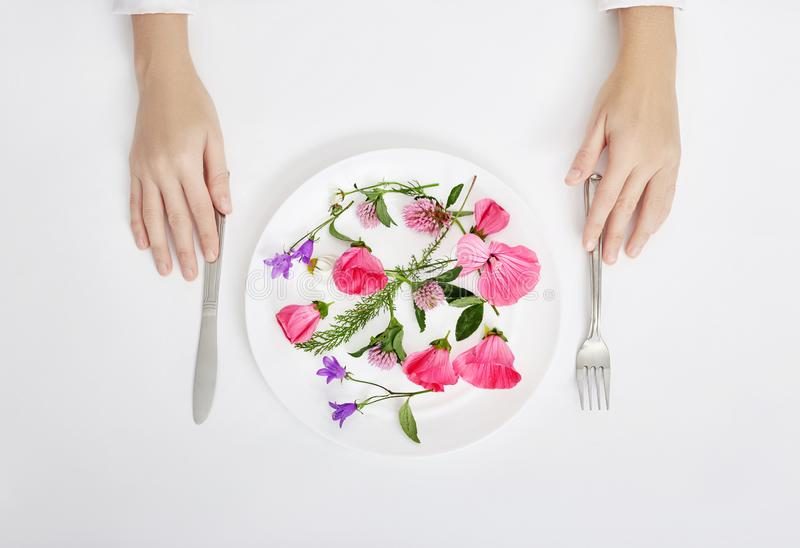 Woman and beautiful spring flowers in plate, hands and skin care, natural cosmetic, summer flower extract. Anti-aging cosmetics. For hands and body, body care stock image