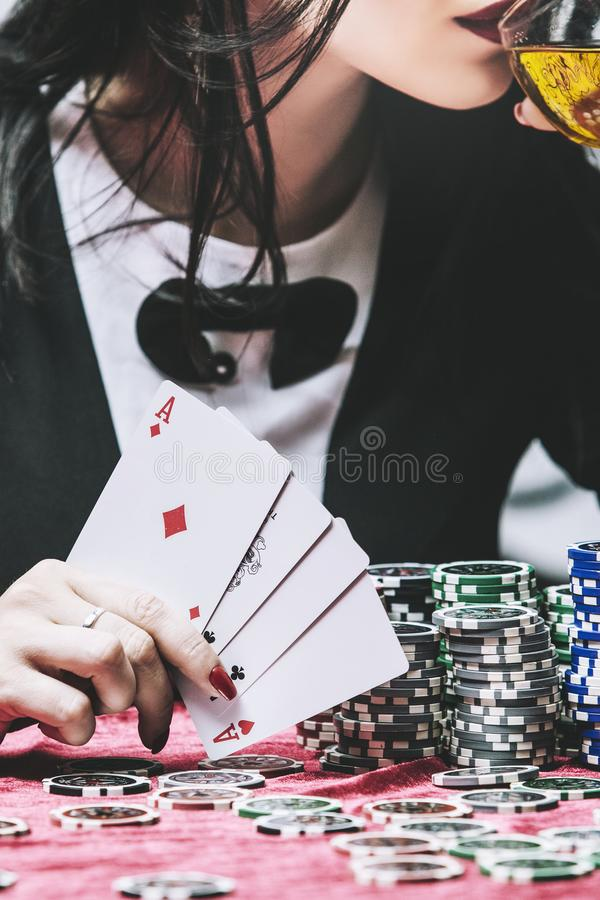 Woman beautiful young successful gambling in a casino at a table. With cards, chips and alcohol closeup