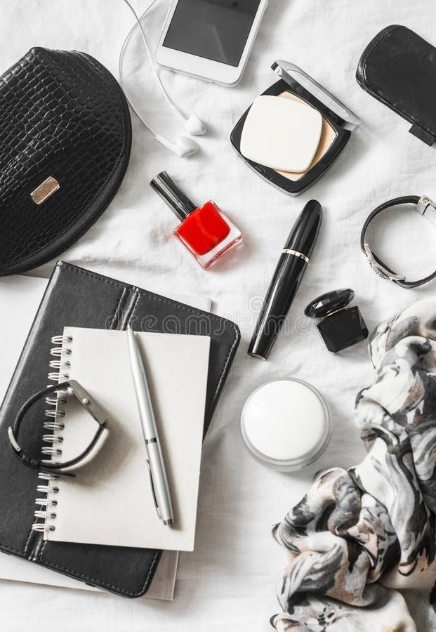 Woman beauty accessories on a light background, top view. Cosmetic bag, red nail polish, mascara, watch, bracelet, scarf, perfume,. Powder, phone, headphones stock photo