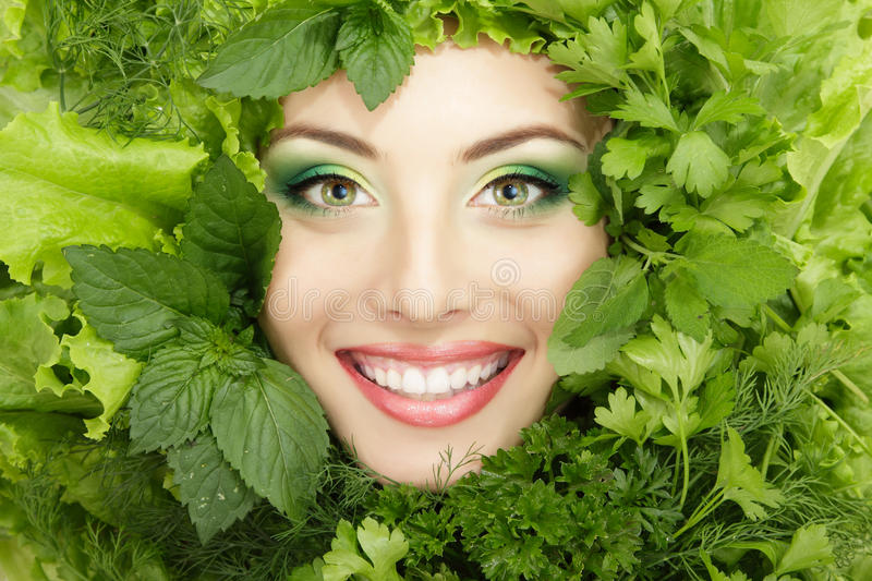 Woman beauty face with greens vegetables frame isolated on white. Background royalty free stock images