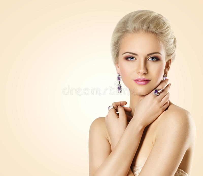 Woman Beauty Face and Jewelry, Beautiful Fashion Model Makeup. Young Girl Make Up and Jewellery, over Beige Background stock photo