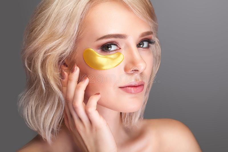Woman Beauty Face With Mask Under Eyes. Beautiful Female With Na. Tural Makeup And Gold Collagen Patches On Fresh Facial Skin. High Resolution royalty free stock images