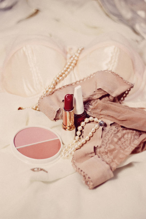 Woman beauty items. Bra, lipstick, nail varnish, stockings, powder and pearls royalty free stock photo
