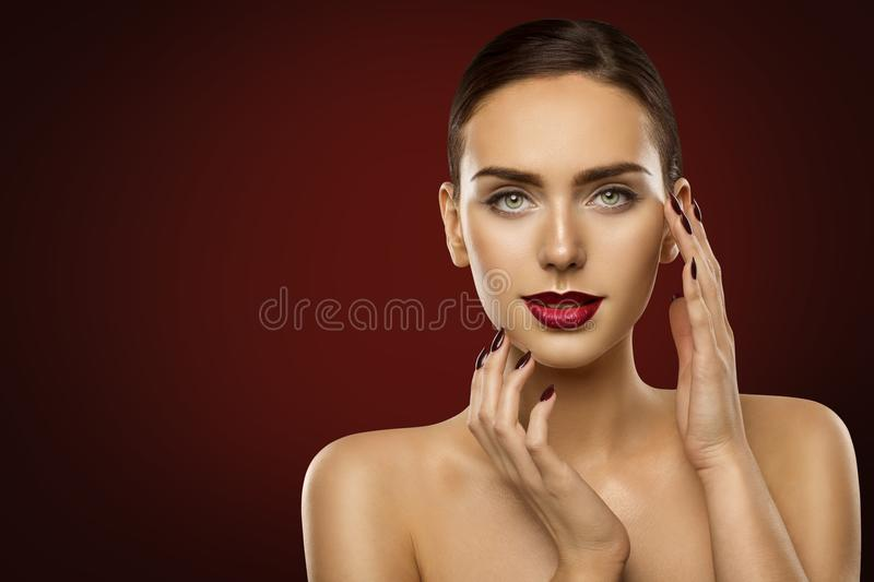 Woman Beauty Makeup, Fashion Model Dark Red Lipstick and Nails. Girl Face over Red background stock photo