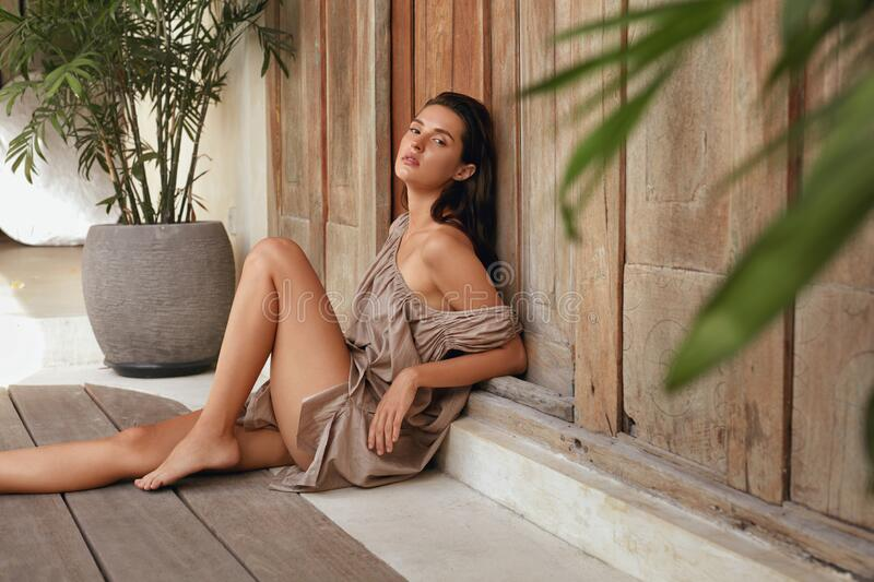 Woman Beauty Portrait. Beautiful Model With Perfect Body Posing Near Wooden Wall On Terrace. Seductive Tanned Brunette. royalty free stock photography