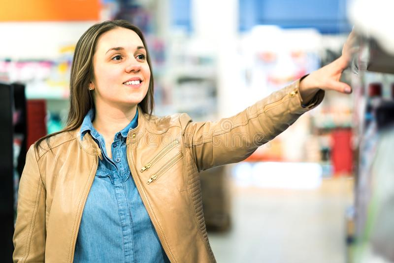Woman at beauty product shelf in supermarket. stock images